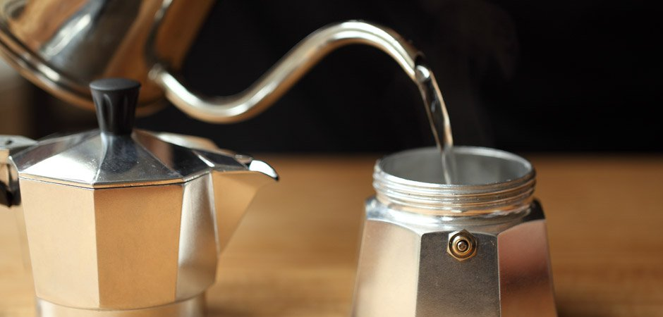 Pouring hot water into the bottom container of the moka pot stovetop coffee maker how to guide.